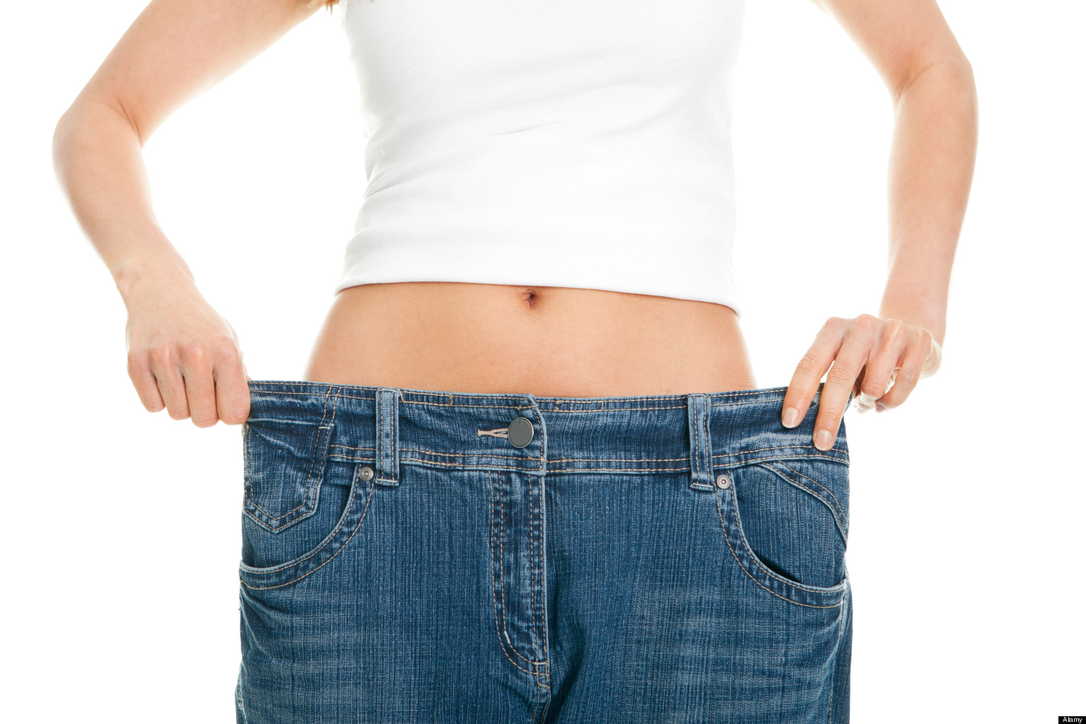 Slim woman pulling oversized jeans. Weight loss concept. Isolated on white