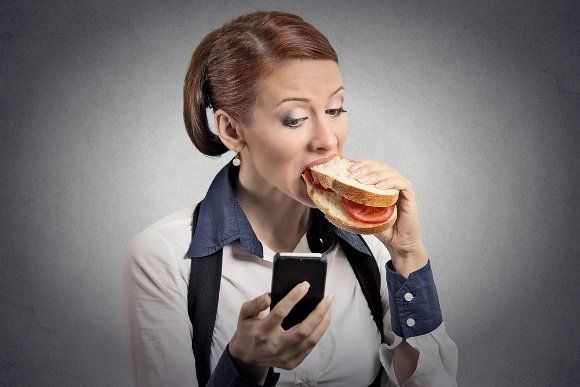 Woman Holding Phone Eating Sandwich